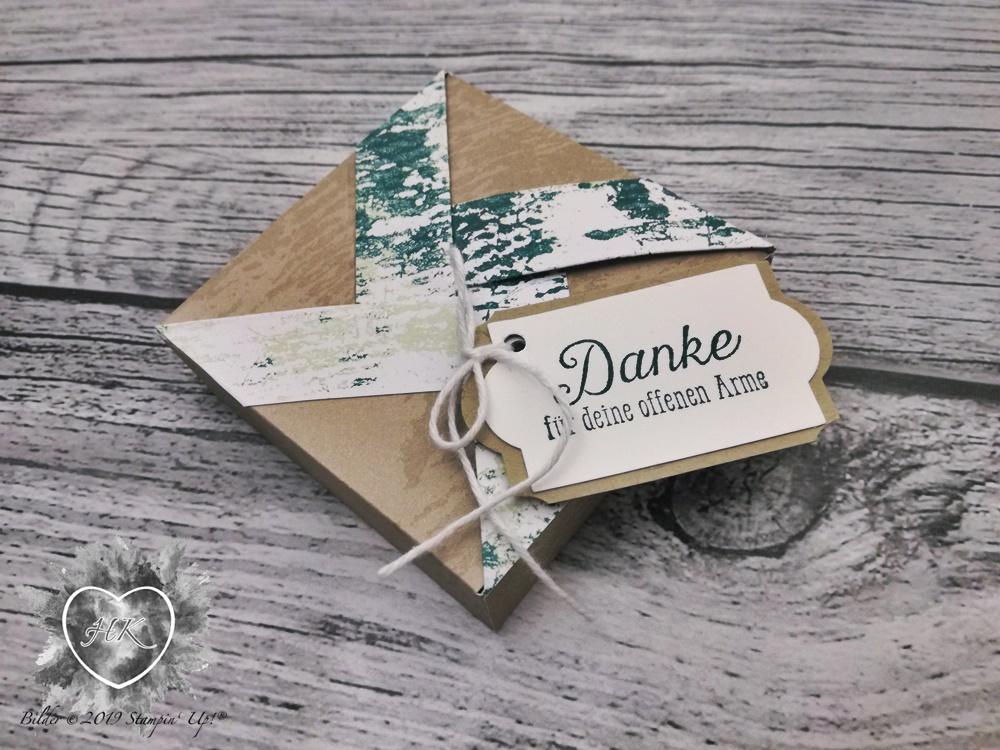 """Heute ist's wieder soweit! Unser Envelope Punch Board Blog Hop ist online! Unser heutiges Thema: Straw Handle Box! Und das habe ich gezaubert: Wie diese Verpackung gemacht wird, zeige ich Euch hier: Für diese Box benötigst du ein Stück Papier nach Wahl mit den Maßen 6"""" x 6"""". 1) Bei 4,3cm und 10,85 cmam Envelope Punch Board anlegen, stanzen und falzen. 2) Das Papier um 90° drehen, bei die Nase an den Falzlinien anlegen, stanzen und falzen. 3) Schritt 1) und 2) wiederholen! Nun eine weitere Falzlinie ziehen (siehe Foto) und.. wie am Foto ersichtlich das Papier von Ausstanzung zu Ausstanzung wegschneiden. Jeweils dort, wo die zusätzliche Falzlinie gezogen wurden. Beim Bodenteil wird nun entlang der Falzlinie (siehe oben) einschneiden. Nun wird Step by Step die Box gebildet. Das letzte Eckerl vollendet den Boden. Die zusätzlich gezogenen Falzlinien müssen nun nach außen gedrückt werden. Somit setzt senkt sich der Deckel. Das überstehende Eckerl wird in die Box gesteckt und verschließt die Box. In die """"Ohren"""" der Box werden nun Löcher gestanzt und ein Strohhalm durch geschoben. Wenn man einen hat der durchs Loch passt. Oder eine Stanze hat, die ein passendes Loch stanzt. Ich hatte keines von beiden. Mein Strohhalmproblem habe ich mit einem Band gelöst. Noch ein wenig Deko oben drauf und fertig ist die fast Strohhalmbox!   Viel Spaß beim nachbauen! Verwendet habe ich folgende Materialien: Farbkarton in Aquamarin und Flüsterweiß Designerpapier Sternenhimmel Kl. Stempelkissen in Aquamarin Stempelset First steps Stanze Kreis 1 1/4"""" Stanze Kreis 1 1/2"""" 5/8"""" (1,6cm) Gepunktetes Tüllband Lackakzente mit Glitzereffekt Epoxi Herzen Wink of Stella Envelope Punch Board Flüssigkleber und Dimensionals Papierschneider und Schere Ich hoffe euch hat mein Projekt gefallen! Aber nun geht's weiter zu xxx! Kreative Grüße Teilnehmer: Elisabeth Pirolt Sandra Herzog - hier bist du gerade Ute Lamprecht Zsuzsánna Balázs Nadine Lange"""